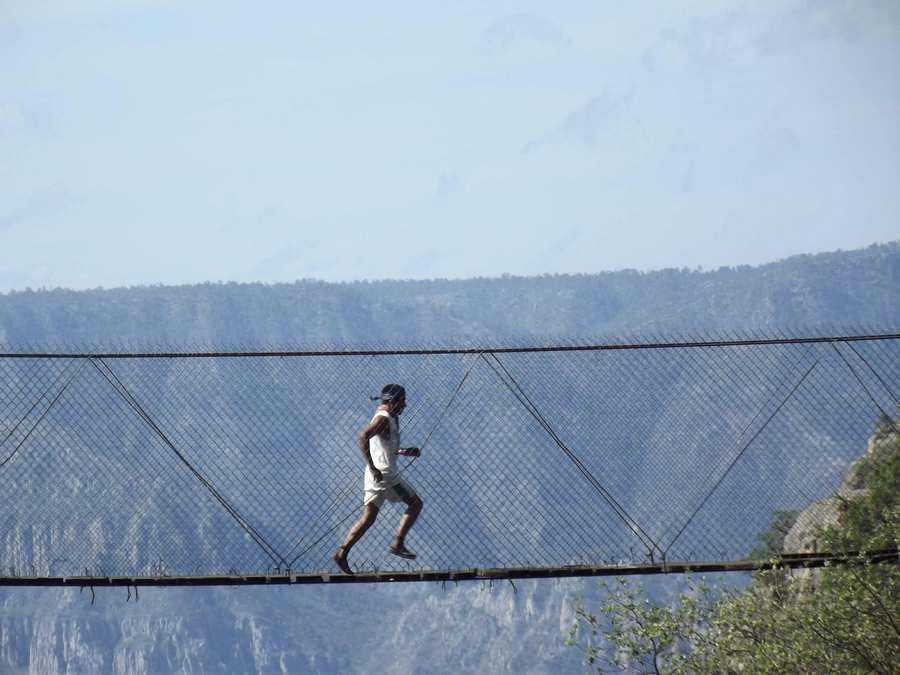 Corredor rarámuri cruzando un puente colgando