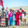 La corredora Aziza Raji animada por un grupo de niños en el Marathon des Sables 2019