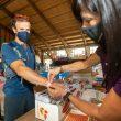 Una voluntaria del Gran Trail Aneto-Posets 2021 le da la pulsera a un participante